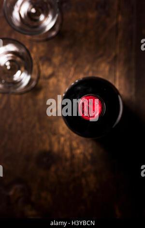 Eine Flasche Wein und zwei Gläser auf Holztisch. Draufsicht mit Textfreiraum. Stockbild