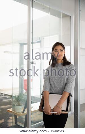 Selbstbewusste, ehrgeizige Geschäftsfrau im Büro Stockbild