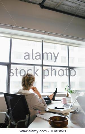 Nachdenklich Geschäftsfrau mit Füßen auf Schreibtisch, Büro Stockbild