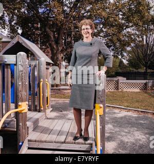 Frau mittleren Alters am Spielplatz Stockbild