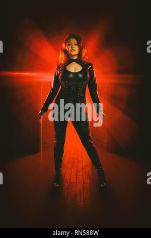Frau steht vor einer Tür mit rotem Licht Stockbild