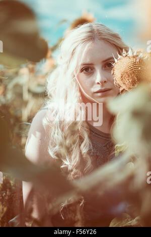 Schöne junge Frau in einem Sonnenblumenfeld an goldene Stunde Stockbild