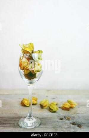 Schöne und elegante Makro Nahaufnahme einer Menge orange leckeres Obst namens Physalis aus Peru, Südamerika, in einem Kristall Glas mit Raum über Holz- ta Stockbild