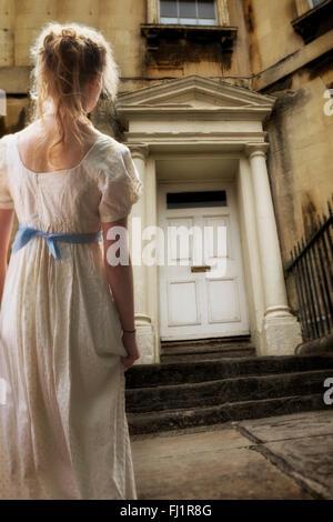 Regency gekleidete Frau warten vor einem regency Stilhaus Stockbild
