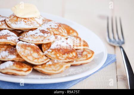 """""""Poffertjes"""": Little Dutch Pancakes mit Butter und Puderzucker. Flache Tiefenschärfe, Fokus auf Klumpen Butter. Stockbild"""