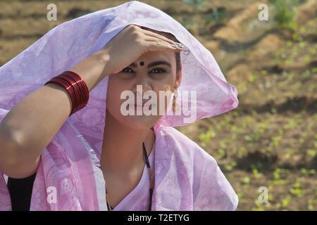 Nahaufnahme eines ländlichen Frau sitzt in ihrer Landwirtschaft Feld über dem Kopf mit Saree mit der Hand in der Nähe von ihrer Stirn Sonnenstrahlen zu decken. Stockbild