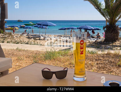 Eine perfekte sonnigen Tag am Strand in Ayia Napa Zypern, einem kalten Keo Bier und Blick auf das blaue Mittelmeer Stockbild
