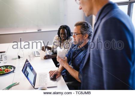 Geschäft Leute an Laptop arbeiten und Essen Mittag zu essen Stockbild
