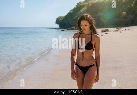 Schuss von attraktiven jungen Frau im Bikini am Strand. Weibliches Model, ein Spaziergang entlang der Küste. Stockbild