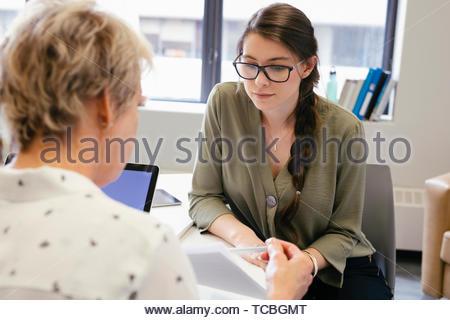 Geschäftsfrauen Schreibarbeit diskutieren in Sitzung Stockbild