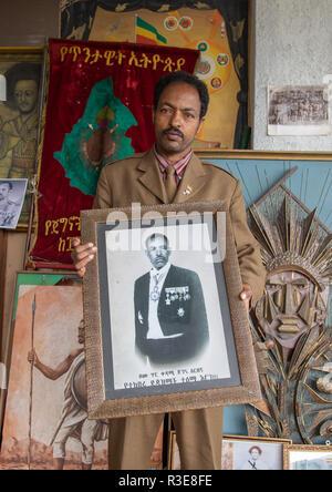 Sekretär der Patrioten in den Krieg Museum hält ein Bild von seinem Vater, Addis Abeba region, Addis Abeba, Äthiopien Stockbild