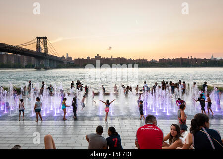 Kinder spielen in den Brunnen mit East River, die Williamsburg Bridge und Manhattans Lower East Side im Hintergrund. Domino Park, Brooklyn, USA Stockbild