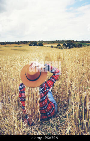 Zurück Blick auf eine junge Frau in einem Feld von Weizen in einem Sommertag Stockbild