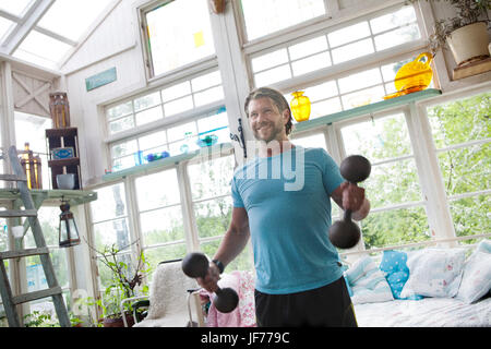 Mitte erwachsenen Mannes Aufhebung Hanteln Stockbild