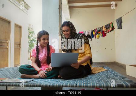 Happy Village Frau mit ihrer Tochter auf einem Feldbett zu Hause zu sitzen und einen Laptop. Stockbild