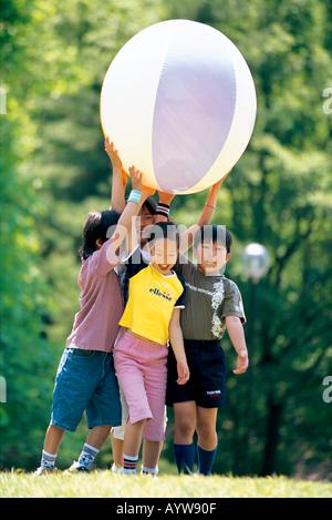 Kinder mit einem großen ball Stockbild