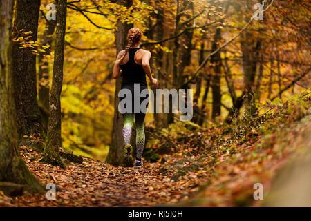 Junge Frau im Wald laufen Stockbild