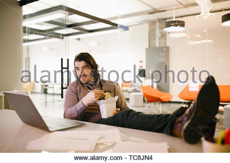 Geschäftsmann mit Füßen mit Laptop und essen Sie Essen in Konferenzraum Stockbild