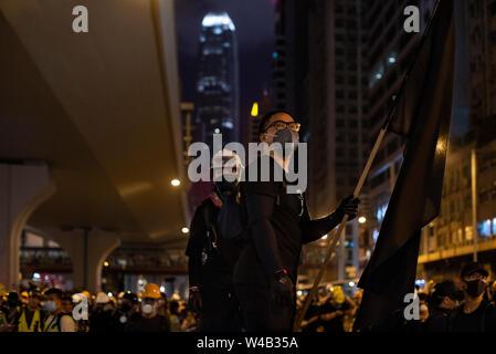 Eine Demonstrantin Wellen eine schwarze Flagge während der Auseinandersetzungen mit der Polizei, Tausende Demonstranten nehmen Sie Teil einer Grosskundgebung fordert unabhängige Untersuchung Polizei Taktik in Hongkong. Stockbild