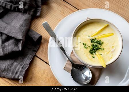 Hohen Winkel in der Nähe der Schüssel Suppe auf hölzernen Tisch. Stockbild