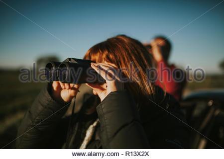 Porträt einer Frau Fernglas Holding Stockbild