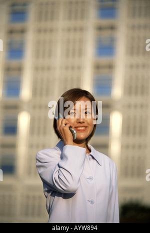 Frau im Gespräch über ein Handy mit hohen Bürogebäude im Hintergrund Stockbild