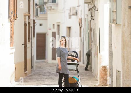 Gallipoli, Apulien, Italien - eine Frau mit einem Kinderwagen in einem mittleren Alter Gasse Stockbild