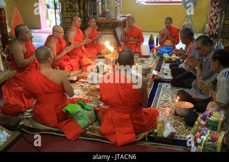 Buddhistische Mönche beten, Sai Sin, die Baumwolle Thread symbolisiert das heilige Band, Wat Simuong (Wat Si Muang), Vientiane, Laos Stockbild