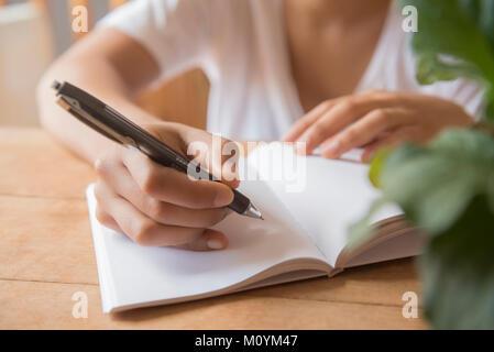 Hände von Afrikanische amerikanische Frau schreiben im Journal Stockbild
