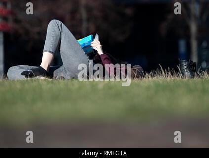 Berlin, Deutschland. 15 Feb, 2019. Liegt eine Frau am Potsdamer Platz in der Sonne ein Buch lesen. Foto: Ralf Hirschberger/dpa/ZB/dpa/Alamy leben Nachrichten Stockbild