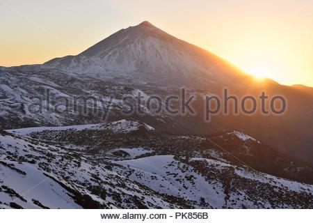 Sonne hinter den Berg Teide (3718 m hohen Gipfel) und der vulkanischen Landschaft der Nationalpark Teide mit Schnee bedeckt. Teneriffa Kanarische Inseln Spanien. Stockbild