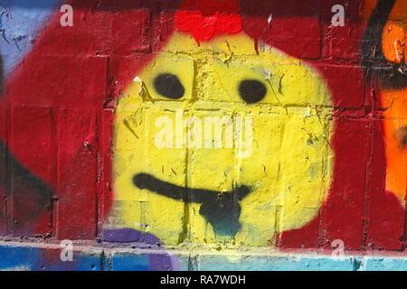 Gelbe smiley, bunte Mauer, Deutschland, Europa ich Gelber smiley, bunte Ziegelsteinmauer, Deutschland, Europa I Stockbild