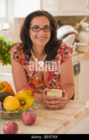 Porträt einer Mitte erwachsenen Frau lächelnd an eine Küchentheke Stockbild
