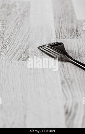 Einzelne Gabel auf Holztisch. Schwarz / weiß Küche Stilleben. Stockbild