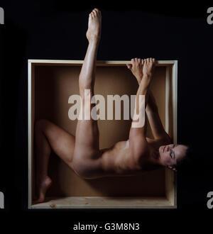 Nackte Frau hängen vom Rand der box Stockbild