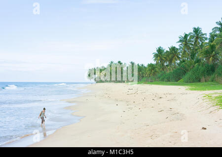 Balapitiya Strand, Sri Lanka - eine junge Frau zu Fuß in die Schwankung am beacof Balapitiya Stockbild