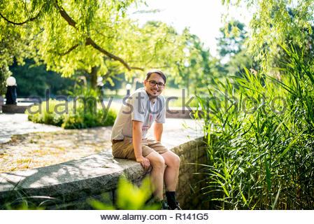 Porträt eines lächelnden Mann sitzt, die von Pflanzen Stockbild