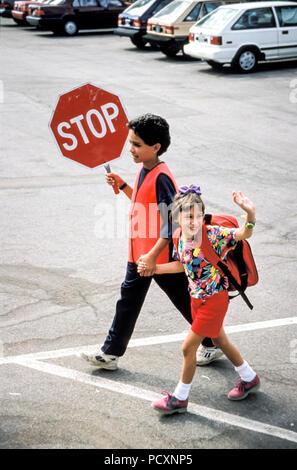 Crossing Guard Sixth grader hilft wenig Mädchen über Parkplatz an der Schule Stockbild