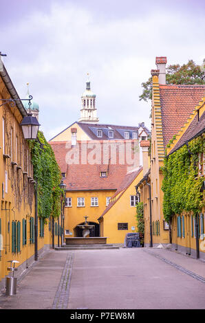Fuggerei, Augsburg, Bayern, Deutschland - Blick durch die Mittlere Gasse Gasse zu den Brunnen und den Perlachturm Tower. Stockbild