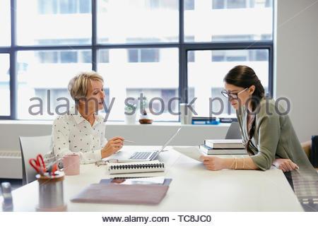 Geschäftsfrauen, die Schreibarbeit im Zimmer Tagung diskutieren Stockbild