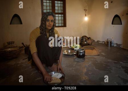 Frau im ländlichen Küche kochen sitzen auf Brennholz mit Utensilien und Gemüse auf dem Boden. Stockbild