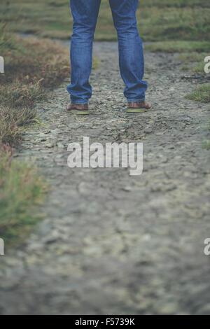 Mannes Beinen stehend auf rissigen Boden Stockbild