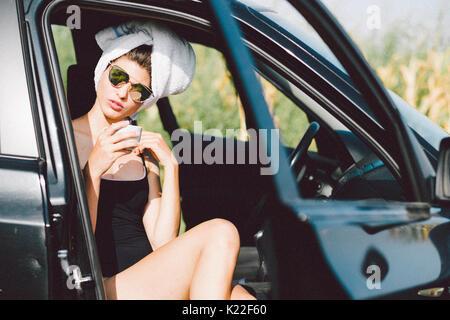 Authentische Frau mit Handtuch auf dem Kopf und Kaffee am Morgen Stockbild