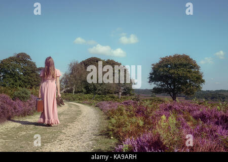 Eine Frau in einem lila Kleid ist ein Spaziergang durch die Heide mit einem Koffer Stockbild