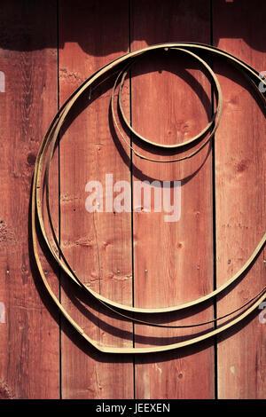 Ländliche Gebäude außen. Metall-Kreise an der Wand hängen. Stockbild