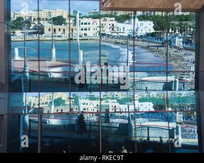St. George's Bay, San ?iljan, Malta einen geschützten Sandstrand in der Nähe von Valetta, reflektierten Mosaik Muster in einer die Fenster eines kommerziellen Gebäude Stockbild