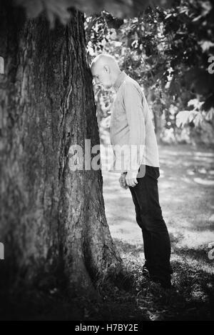 Porträt des alten Mannes an einen Baum gelehnt. Konzept des Alters und Natur. Ruhestand und Frustration. Stockbild