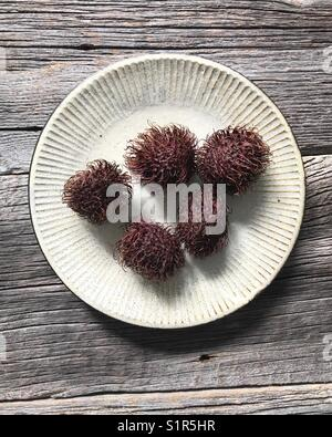 Rambutan auf einer Keramikplatte Stockbild