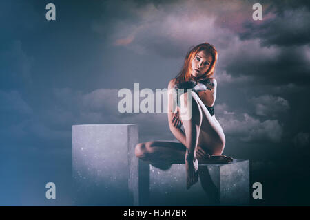 Rote Haare Frau sitzt auf einer Reihe von weißen Felder in der Nacht Stockbild