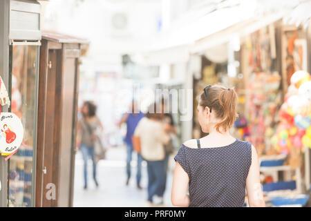 Otranto, Apulien, Italien - eine Frau, die zu Fuß durch die Fußgängerzone von Otranto in Italien Stockbild